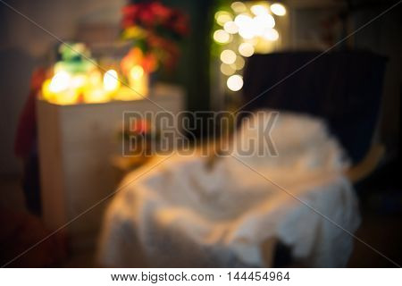 Beautiful Christmas decoration with lights and comfortable chair. It is out of focus and suitable for background