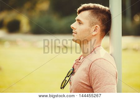 Masculinity handsome outdoor concept. Relaxed boy leaning on pole. Young man chilling in park.
