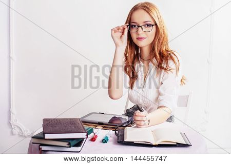 woman in glasses with the tablet and notebook. The concept of business or education