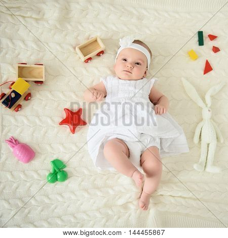 Too cute for words. Shot of adorable baby girl lying on bed near toy and looking on camera