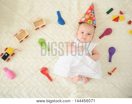 My first birthday. Top view of little baby girl wearing in party hat and lying on blanket with toys around