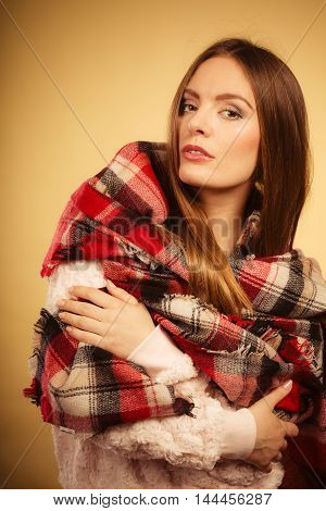 Fashion warm clothing concept. Beautiful model with winter clothes. Attractive woman wearing checkered scarf and thick sweather.