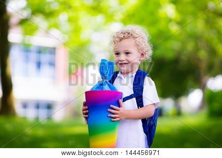 Happy child holding traditional German candy cone on the first school day. Little student with backpack and books excited to be back to school. Beginning of class in Germany with sweets for kids.