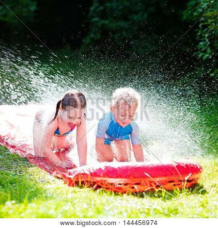 Little girl and boy playing with garden water slide. Children jumping and splashing with gardening hose. Outdoor summer fun with backyard sprinkler for kids on hot sunny day.