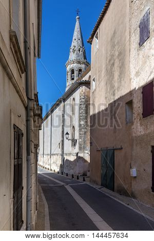 Typical narrow street in in Saint-Saturnin-les-Apt (France) with church tower in background.