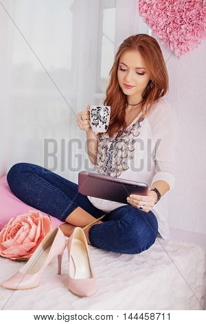young beautiful girl with a tablet. The concept of lifestyle