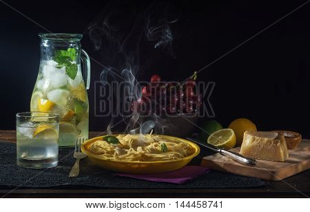 Still life with pasta, parmesan, grapes and ice cold lemon drink in a glass jar on dark background