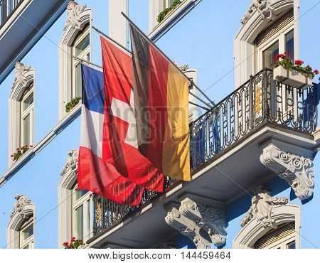 Basel, Switzerland - 27 August, 2016: balcony of the Grand Hotel Euler building decorated with flags of France, Germany and Switzerland. Basel is a city in Switzerland, located where borders of France, Germany and Switzerland meet.