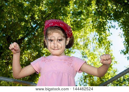 A silly young girl looks at the camera with a crazy facial expression. She is holding her fists up wearing a red bandana and is in front of backlit trees and a blue sky.
