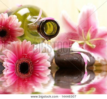 Bottle of massaging oil over spa background (only part of bottle and foreground flowers are in focus)