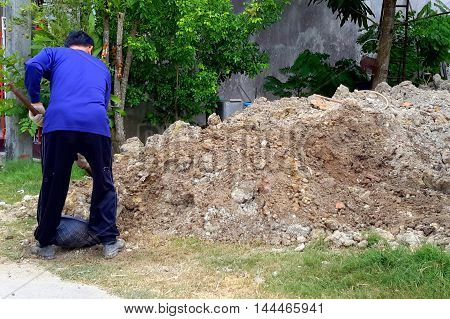 middle-aged man blue sweatshirt digging pile of dirt hoe home improvement construction grass black plastic basket trees flower garland junk hose green brown gray,dig working work shoes garden exercise