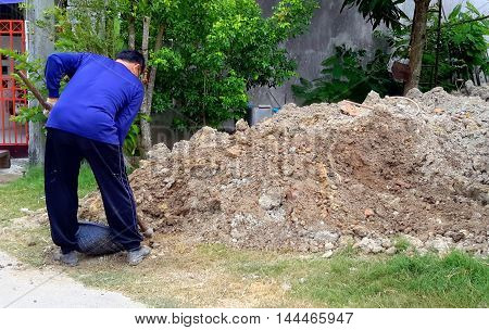 middle-aged man in blue sweatshirt digging in a pile of dirt with a hoe at a home improvement construction area, Songkhla, Thailand