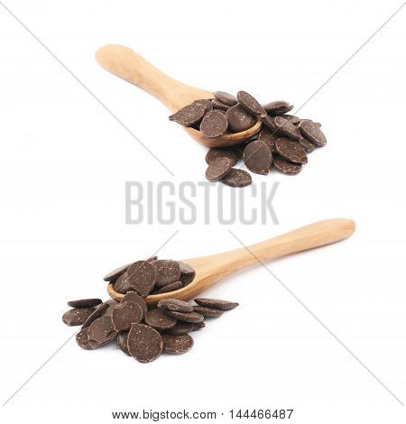Pile of cooking chocolate teardrop shaped chips with a serving wooden spoon over it, composition isolated over the white background, set of two different foreshortenings