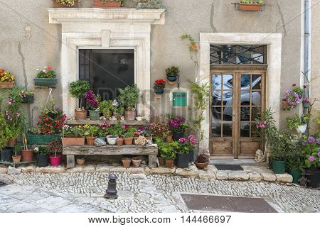 Street with greenery in flower pots on the floor and the walls in Saint-Saturnin-les-Apt France