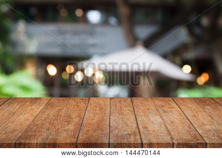 Perspective brown wooden table top with cafe blurred abstract background