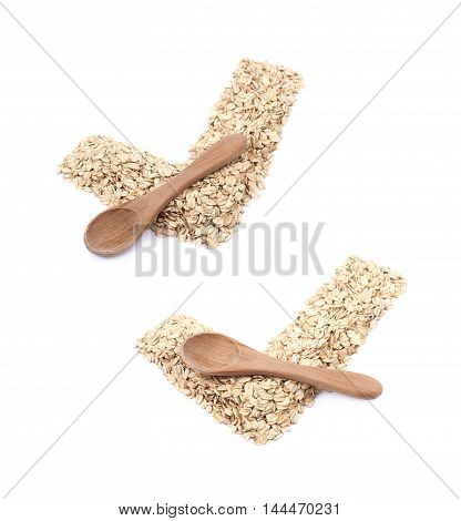 Yes tick shape made of oatmeal flakes with a wooden spoon over it, composition isolated over the white background, set of two different foreshortenings