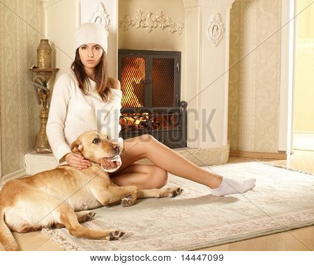 Attractive woman with the dog over fireplace