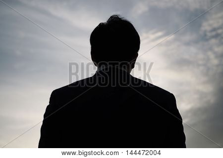 Back Of Businessman In Silhouette With Sunset Background