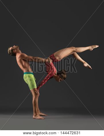 Acrobatic duo posing while practicing in studio, on gray background