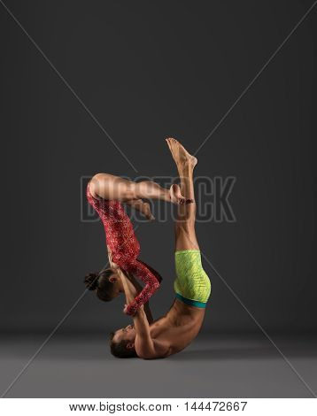 Sport. Duo of gymnasts exercising at camera, on gray background