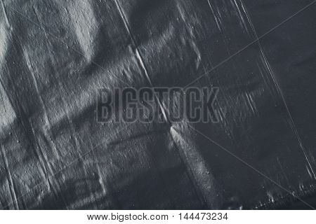 Close-up fragment of a black polyethylene trash bag's surface as a backdrop texture composition