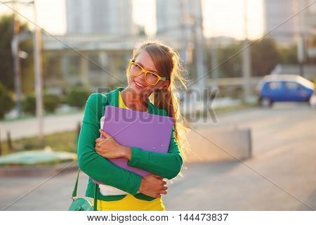 Business girl with a folder in her hands. Girl in glasses and jacket smiles.