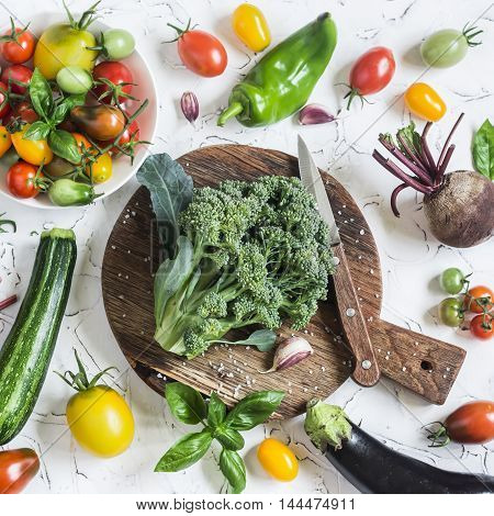 Fresh vegetables on a light background - broccoli tomatoes peppers beets eggplant radish. Vegetarian table. Raw ingredients