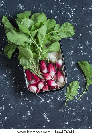 Fresh radishes in a metal bowl on a dark background