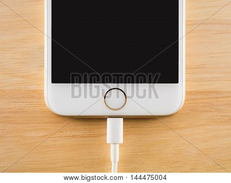 CHIANGRAI THAILAND -JULY 28 2016: Top view image of the Apple iPhone 6S charging with Lightning USB Cable on the wooden table on July 28 2016 in Chiangrai Thailand.