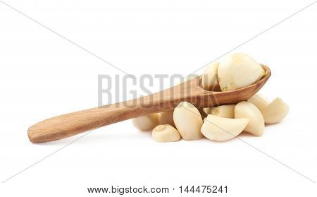 Pile of peeled garlic with the wooden spoon over it, composition isolated over the white background