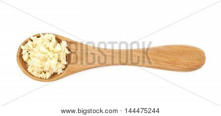 Wooden spoon of minced garlic isolated over the white background