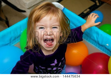 A wild eyed little girl laughs up at the camera. She is standing in a playpen surrounded by balloons.