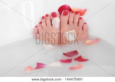 Woman legs with flower petals in bathtub