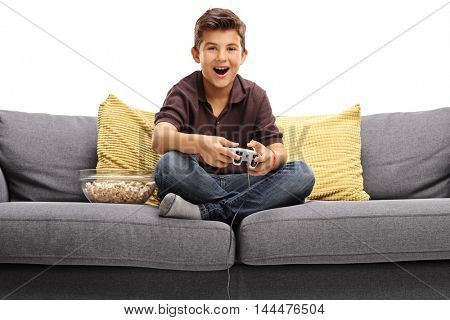 Cheerful boy sitting on a sofa and playing video games isolated on white background