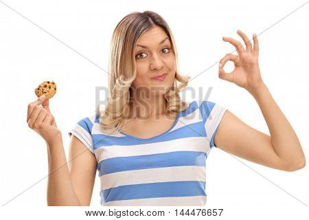 Cheerful woman eating a cookie and making an ok sign isolated on white background