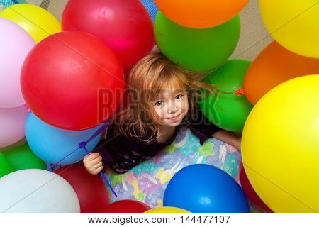 A little girl plays in a pile of balloons. she looks happy and almost like she is trying to hold her breath.