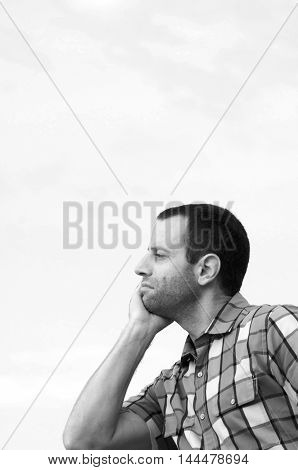 Black and white photo of a man looking out with his face leaning against his hand wearing a plaid shirt.