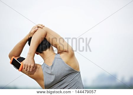 young asian male jogger with fitness tracker attached to arm warming up by stretching arms and upper body before running.