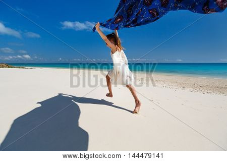 Cute little girl having fun running with sarong and enjoying vacation at tropical beach with white sand and turquoise ocean water