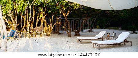 Panorama of a wooden lounge chairs on a beautiful tropical beach