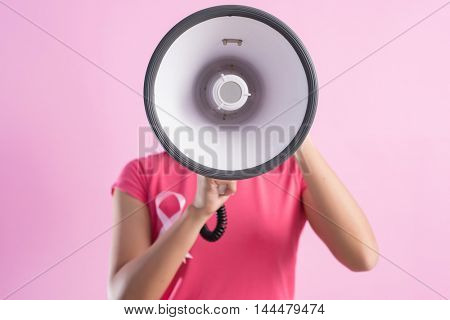 healthcare and medicine concept - woman with pink breast cancer awareness ribbon and a bullhorn
