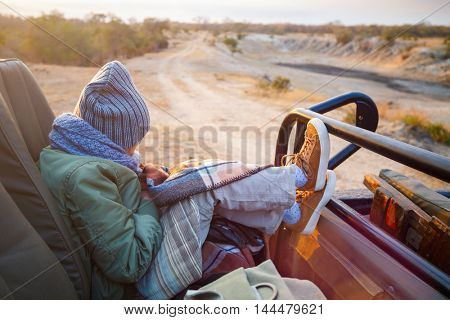 Adorable little girl wearing warm clothes outdoors on beautiful winter morning safari game drive