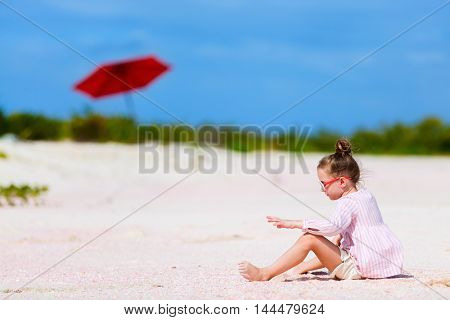 Adorable little girl playing with sand and shells on unique pink sand beach on Barbuda tropical island in Caribbean