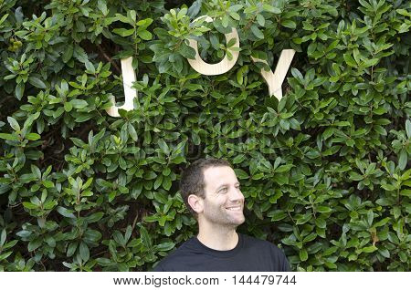Man standing outside under wooden letters that spell out the word joy wearing a black shirt with a smile on his face.