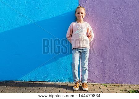 Adorable little girl outdoors against colorful house in Bo Kaap Quarter in Cape Town