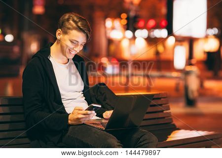 Smiling guy reading message on smartphone, while he working on laptop outside. Young male freelancer working in city street in night time, blurred lights background, free space