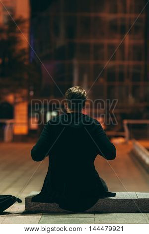 Man sitting in night street, back view. Rear of guy having rest at city street at square, dreaming about something, free space