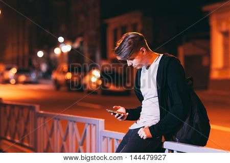 Young man reading smartphone outside. Attractive guy with bag sitting on street fence with phone. Technology addiction concept