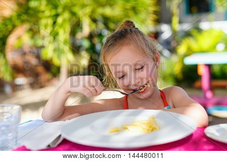 Portrait of adorable little girl eating pasta for a lunch at restaurant