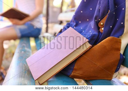 Backpack and book on bench in park, close up